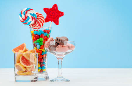 Various sweets assortment. Candy, bonbon, chocolate and macaroons in cocktail glasses over blue background. With copy space