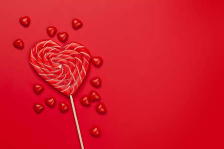 Valentines day greeting card template. Heart candy sweets over red background. Top view flat lay with copy space