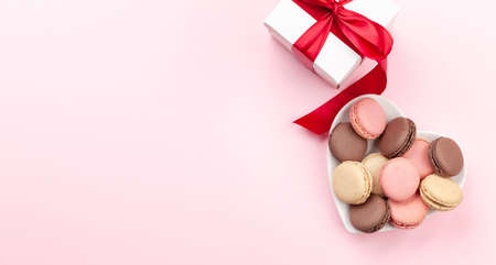 Valentines day with macaroons in heart shaped plate and gift box over pink background with copy space. Top view flat lay