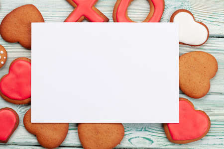 Valentines day greeting card over gingerbread cookies. Top view flat lay with copy space