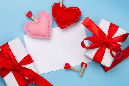Valentines day greeting card template. Gift boxes and heart shaped decor over blue background. Top view flat lay with copy space