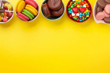 Various sweets assortment. Candy, bonbon and macaroons on yellow background. Top view flat lay with copy space Standard-Bild