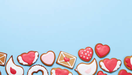 Valentines day greeting card with heart shaped gingerbread cookies over blue. Top view flat lay with copy space