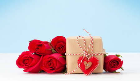 Valentines day greeting card with red rose flowers bouquet and gift box on wooden table. With space for your greetings