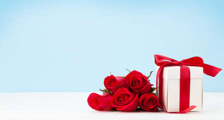 Valentines day greeting card with red rose flowers bouquet and gift box on wooden table. With space for your greetings Imagens - 162298786