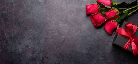 Valentines day greeting card with red rose flowers bouquet and gift box on stone table. Top view flat lay with space for your greetings Imagens - 162298796
