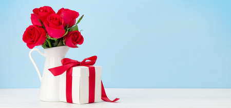 Valentines day greeting card with red rose flowers bouquet and gift box on wooden table. With space for your greetings Imagens - 162298807