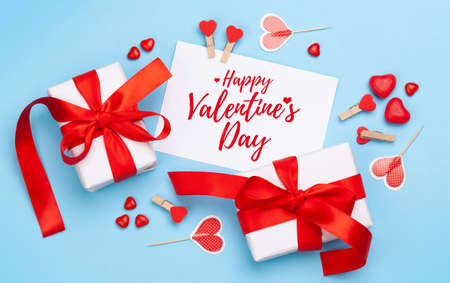 Valentines day greeting card. Gift boxes, heart decor and candy sweets over blue background. Top view flat lay Imagens - 162298811