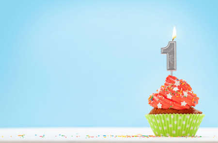 Birthday cupcake with number one burning candle over blue background with copy space for your greetings Imagens - 162298817