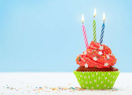 Birthday cupcake with three burning candles over blue background with copy space for your greetings Imagens - 162298818