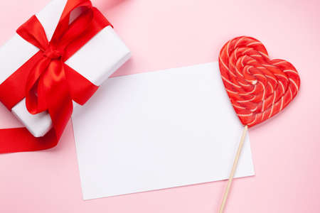 Valentines day greeting card template. Gift box and heart candy lollipop over pink background. Top view flat lay with copy space Imagens - 162298819