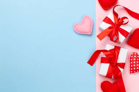 Valentines day greeting card template. Gift boxes and heart shaped decor over blue and pink background. Top view flat lay with copy space Imagens - 162298864