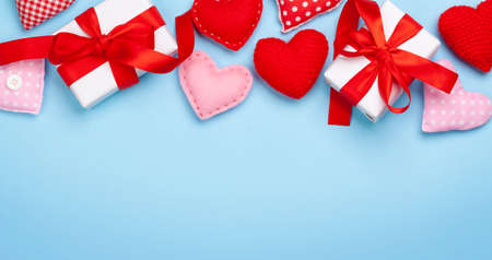 Valentines day greeting card template. Gift boxes and heart shaped decor over blue background. Top view flat lay with copy space Imagens - 162298865