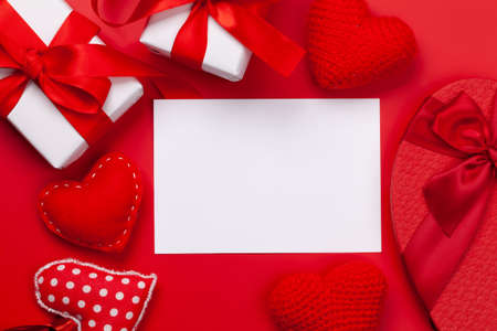 Valentines day greeting card template. Gift boxes and heart shaped decor on red background. Top view flat lay with copy space Imagens - 162298873