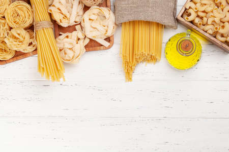Various types of Italian pasta and olive oil on wooden table. Top view flat lay with copy space Imagens - 162298877