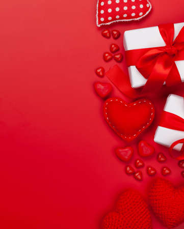 Valentines day greeting card template. Gift boxes, heart decor and candy sweets over red background. Top view flat lay with copy space Imagens - 162298895