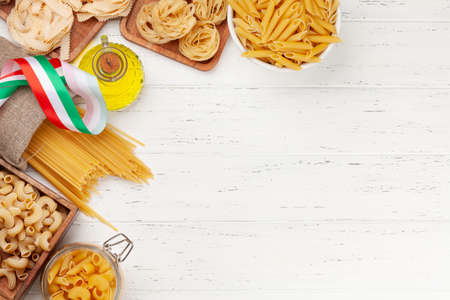Various types of Italian pasta and olive oil on wooden table. Top view flat lay with copy space Imagens - 162298906