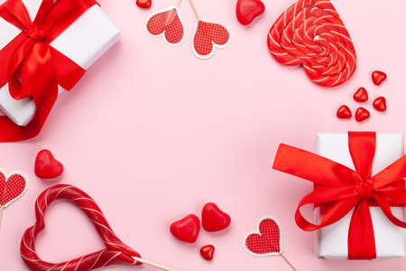 Valentines day greeting card template. Gift boxes, heart decor and candy sweets over pink background. Top view flat lay with copy space Imagens - 162298917