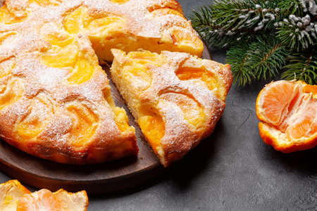 Citrus dessert holiday cake, tangerines and christmas fir tree Imagens - 162298927