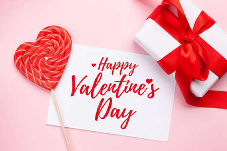 Valentines day greeting card. Gift box and heart candy lollipop over pink background. Top view flat lay Imagens - 162298949