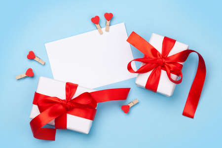 Valentines day greeting card template. Gift boxes and heart decor over blue background. Top view flat lay with copy space Imagens - 162298957