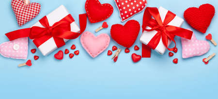 Valentines day greeting card template. Gift boxes, heart decor and candy sweets over blue background. Top view flat lay with copy space Imagens - 162298962