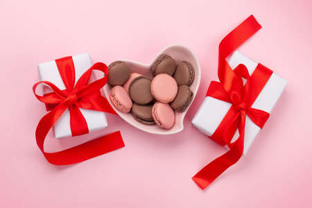 Valentines day with macaroons in heart shaped plate and gift boxes over pink background. Top view flat lay Imagens - 162298965