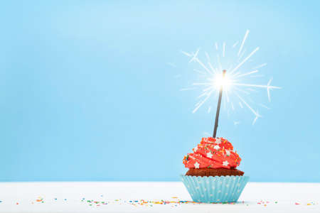 Birthday cupcake with burning sparkler over blue background with copy space for your greetings Imagens - 162298970