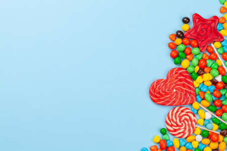 Various sweets assortment. Candy, bonbon and lollipops on blue background. Top view flat lay with copy space Imagens - 162298971
