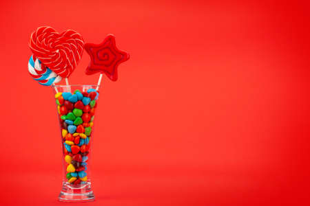 Various sweets assortment. Candy, bonbon, chocolate and macaroons in cocktail glass over red background. With copy space Imagens - 162298974