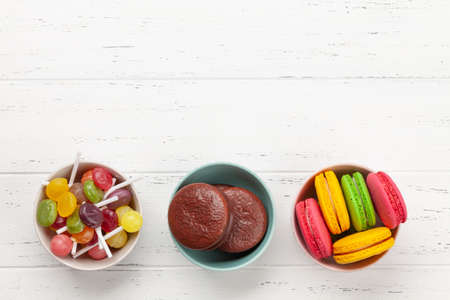 Various sweets assortment. Candy, bonbon and macaroons on wooden background. Top view flat lay with copy space Imagens - 162298976