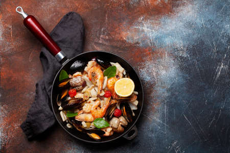 Mixed grilled seafood. Various roasted shrimps, mussels and shellfish in frying pan. Top view flat lay with copy space 免版税图像
