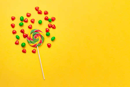 Various sweets assortment. Candy and lollipops on yellow background. Top view flat lay with copy space 免版税图像