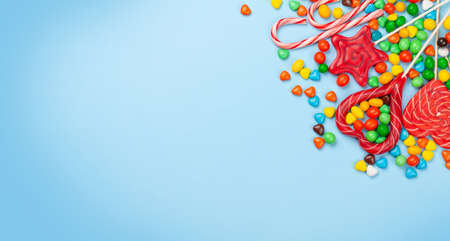 Various sweets assortment. Candy, bonbon and lollipops on blue background. Top view flat lay with copy space 免版税图像