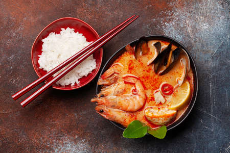 Traditional Thai soup Tom Yum kung with seafood, coconut milk and chili pepper and rice bowl. Top view flat lay 免版税图像