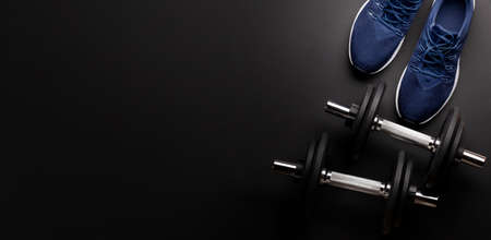 Sneakers and dumbbells. Sport, fitness and healthy lifestyle background. Top view flat lay with copy space 免版税图像
