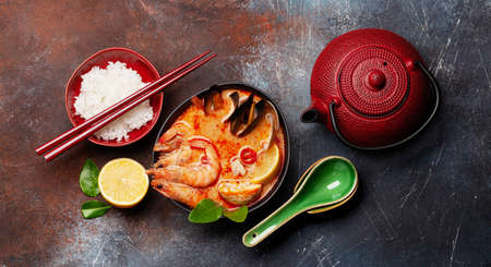 Traditional Thai soup Tom Yum kung with seafood, coconut milk and chili pepper, rice bowl and teapot. Top view flat lay