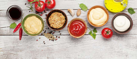 Set of various sauces. Popular sauces in bowls - ketchup, mustard, mayonnaise on white wooden table. Top view flat lay 免版税图像