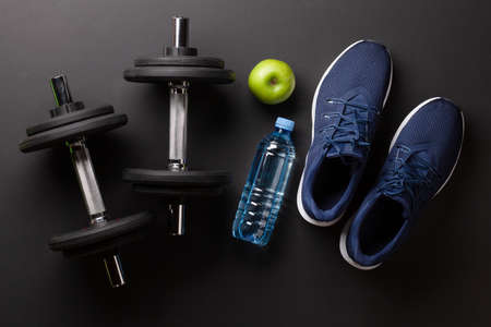 Sneakers, food and dumbbells. Sport, fitness and healthy lifestyle concept. Top view flat lay