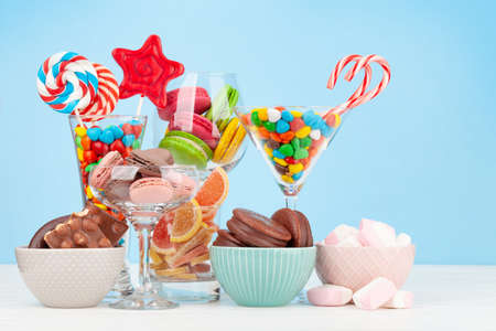 Various sweets assortment. Candy, bonbon, chocolate and macaroons in cocktail glasses over blue background