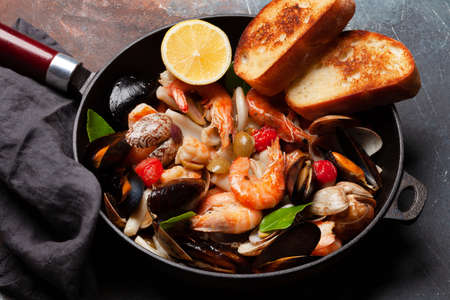 Mixed grilled seafood. Various roasted shrimps, mussels and shellfish in frying pan