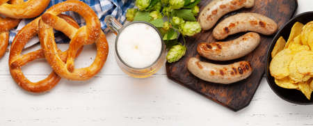 Oktoberfest set. Pretzels, sausages and lager beer mug on wooden background. Top view flat lay