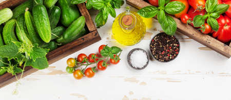 Fresh garden tomatoes and cucumbers with herbs cooking on wooden table. Top view flat lay