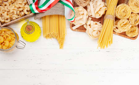 Various types of Italian pasta and olive oil on wooden table. Top view flat lay with copy space