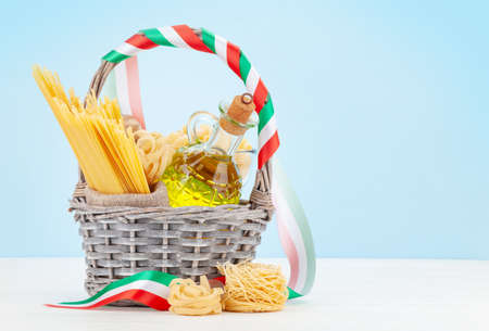 Various types of Italian pasta, olive oil and copy space