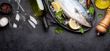 Raw fish cooking. Seafood and white wine on stone table. Top view flat lay 免版税图像