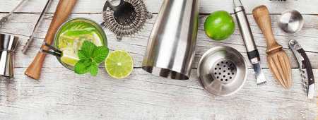 Cocktail utensils. Set of bar tools and mojito cocktail on wooden table. Top view flat lay Stock fotó