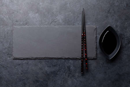 Stone plate and chopsticks for your sushi and maki. Japanese food menu backdrop. Top view flat lay with copy space