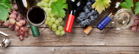 Wine bottles, glasses and grapes on wooden table. Top view flat lay 免版税图像
