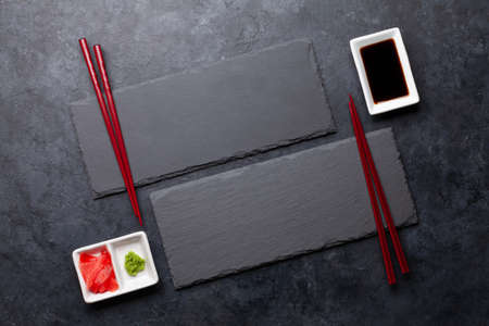 Stone plates and chopsticks for your sushi and maki. Japanese food menu backdrop. Top view flat lay with copy space